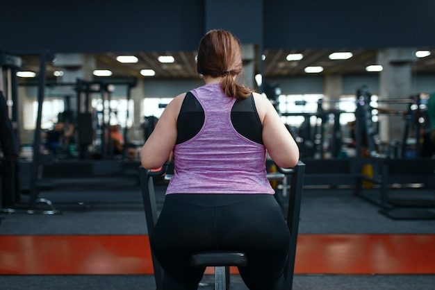 ジム、背面図、アクティブなトレーニングで運動をしている太りすぎの女性