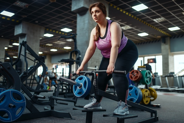 Overweight woman doing exercise with bar in gym, active training.
