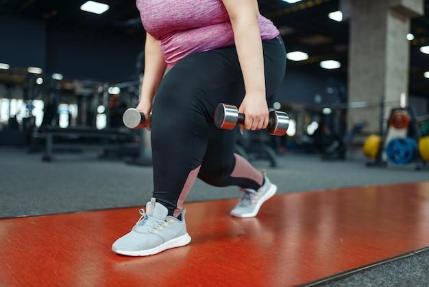 ジムでダンベルを使った運動をしている太りすぎの女性、アクティブなトレーニング。肥満の女性は、太りすぎ、肥満に対する有酸素運動に苦しんでいます