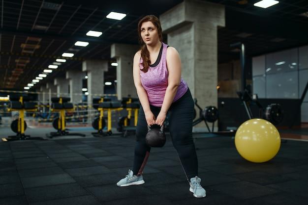 ジムでケトルベルを使った運動をしている太りすぎの女性、アクティブなトレーニング。太りすぎの女性は、太りすぎ、肥満に対する有酸素運動、スポーツ クラブに苦しんでいます