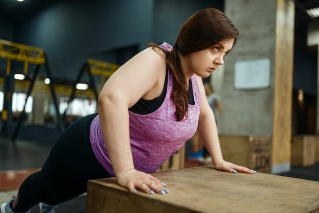 ジムで腕立て伏せ運動をしている太りすぎの女性、アクティブなトレーニング。太りすぎの女性は、太りすぎ、肥満に対する有酸素運動、スポーツ クラブに苦しんでいます