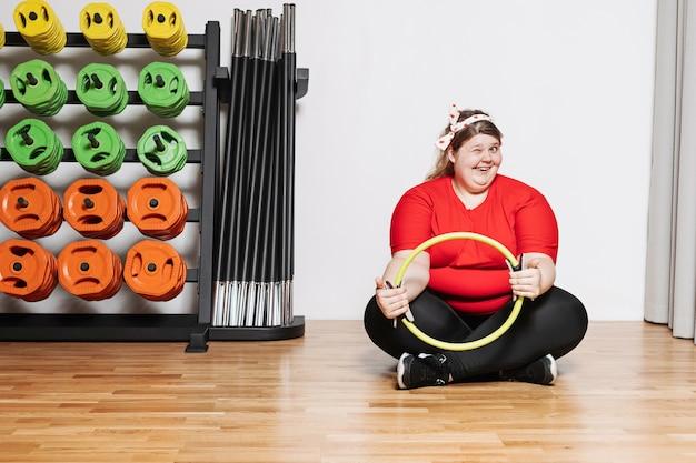 スポーツウェアを着た太りすぎの女性は、他のスポーツ用品の隣のジムでピラティスリングを使って運動することはほとんどありません