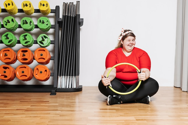 Overweight woman dressed in the sports wear is hardly working out with pilates ring in the gym next to other sports equipment