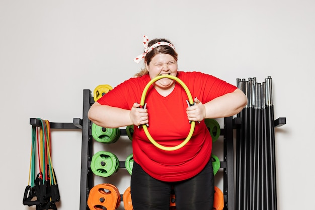Overweight woman dressed in sportswear is hardly working out with pilates ring the in the gym