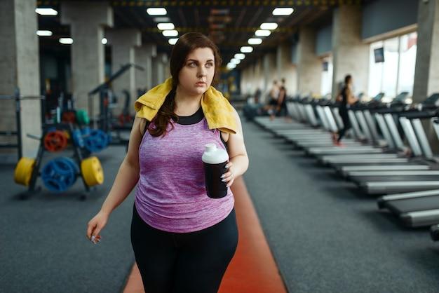太りすぎの女性は、ジムでダイエット カクテルを飲み、アクティブ トレーニングを行います。太りすぎの女性は、太りすぎ、肥満に対する有酸素運動、スポーツ クラブに苦しんでいます