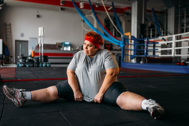 Overweight woman, exercises on the floor, workout in gym. calories burning, obese female person, training in sport club
