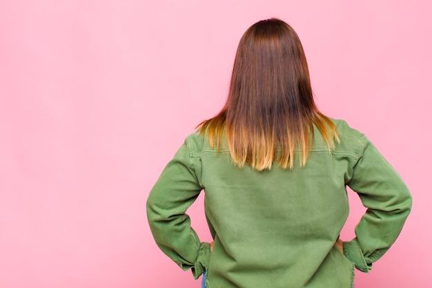 Женщина с избыточным весом, чувствуя смущение или чувство полноты, или сомнения и вопросы, недоумевая, с руками на бедрах, вид сзади