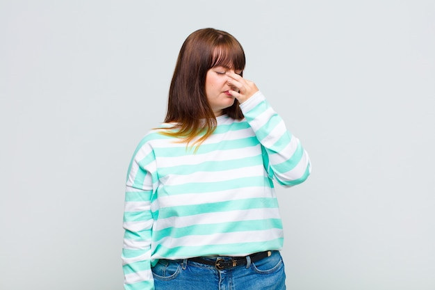 Overweight woman feeling disgusted, holding nose to avoid smelling a foul and unpleasant stench