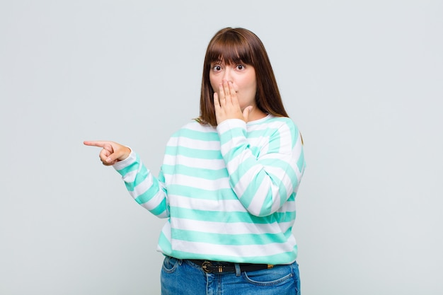 Overweight woman feeling happy, shocked and surprised, covering mouth with hand and pointing to lateral copy space