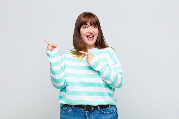 과체중 여성이 즐겁고 놀란 느낌, 충격적인 표정으로 웃고 측면을 가리키는
