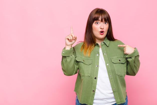 Overweight woman feeling proud and surprised, pointing to self confidently, feeling like successful number one