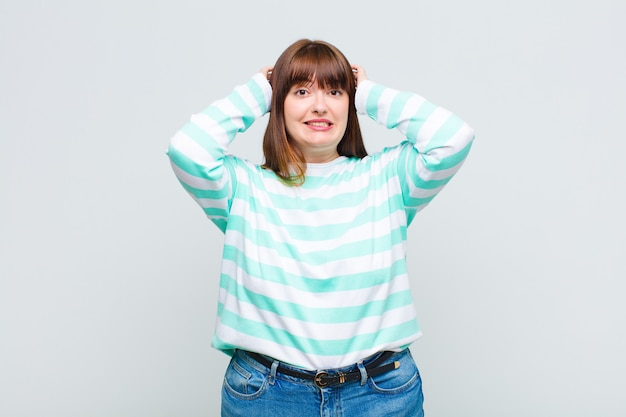 Overweight woman feeling stressed, worried, anxious or scared, with hands on head, panicking at mistake