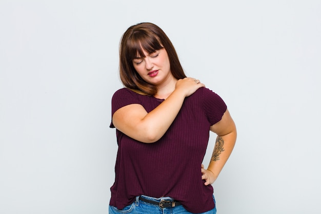 Overweight woman feeling tired, stressed, anxious, frustrated and depressed, suffering with back or neck pain