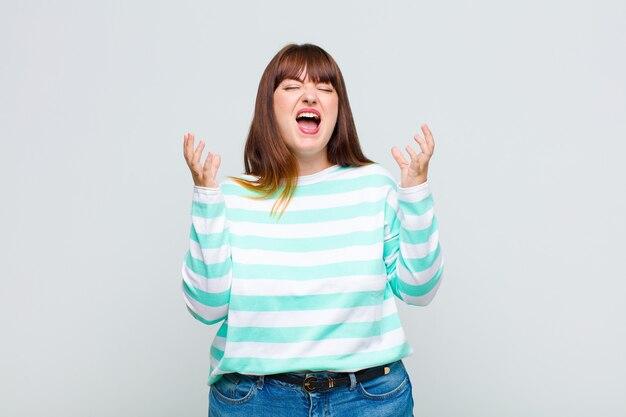太りすぎの女性が猛烈に叫び、ストレスを感じ、空中に手を上げてイライラし、なぜ私が