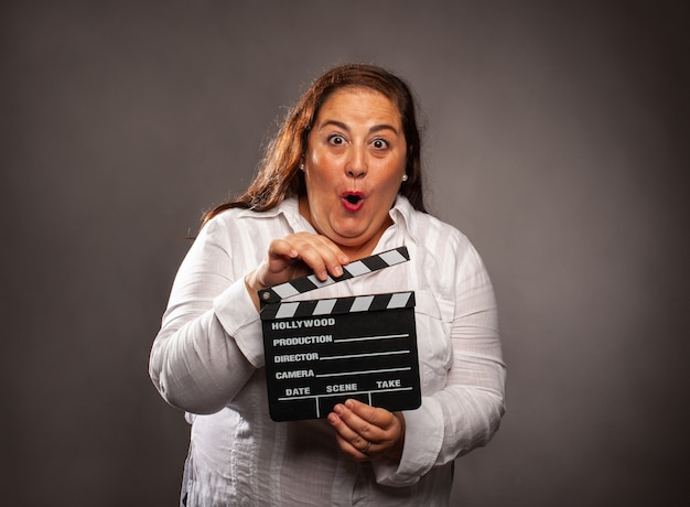 Overweight woman holding a movie clapper board on a grey background