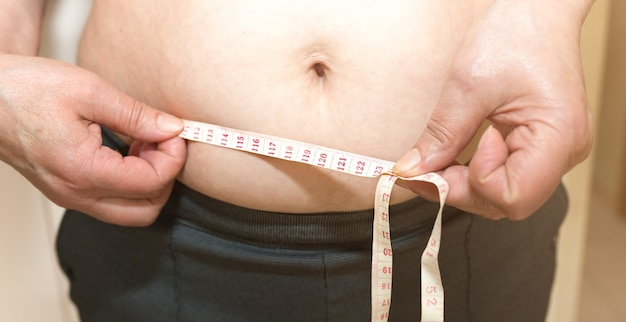 Overweight woman is measuring her waist. fat belly with centimeter with tape measure.