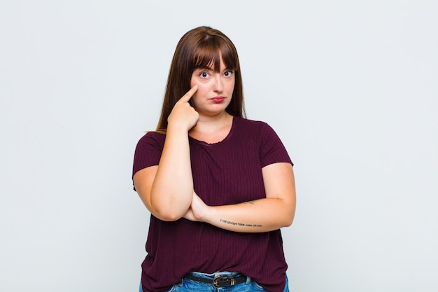 Overweight woman keeping an eye on you, not trusting, watching and staying alert and vigilant