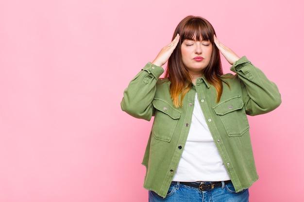 집중되고 사려 깊고 영감을 얻은 과체중 여성이 이마에 손을 대고 브레인 스토밍하고 상상합니다.