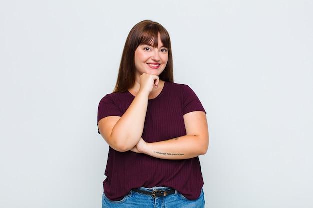 과체중 여성이 행복하고 턱에 손을 대고 웃고, 궁금해하거나 질문하고, 옵션을 비교합니다.