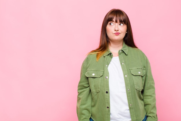 Overweight woman looking puzzled and confused, wondering or trying to solve a problem or thinking