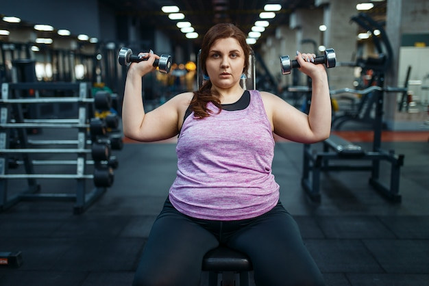 Overweight woman poses with dumbbells in gym, active training.