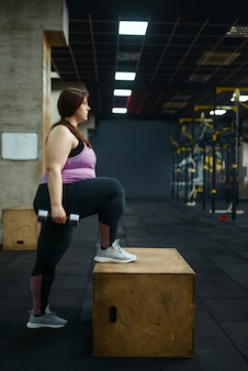 Overweight woman poses with dumbbells in gym, side view, active training. obese female person struggles with excess weight, aerobic workout against obesity, sport club