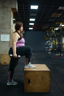 Полная женщина позирует с гантелями в тренажерном зале, вид сбоку, активные тренировки. тучная женщина борется с лишним весом, аэробная тренировка против ожирения, спортивный клуб