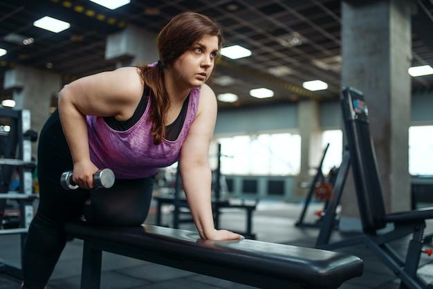太りすぎの女性は、ジムのブランチにダンベルを付けてポーズをとり、アクティブなトレーニングを行う。太りすぎの女性は、太りすぎ、肥満に対する有酸素運動、スポーツ クラブに苦しんでいます