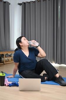 Женщина с избыточным весом отдыхает и пьет воду после занятий дома.