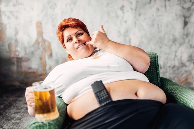 과체중 여자 의자에 앉아 맥주, 폭식증, 비만을 마신다. 건강에 해로운 생활 방식, 뚱뚱한 여성
