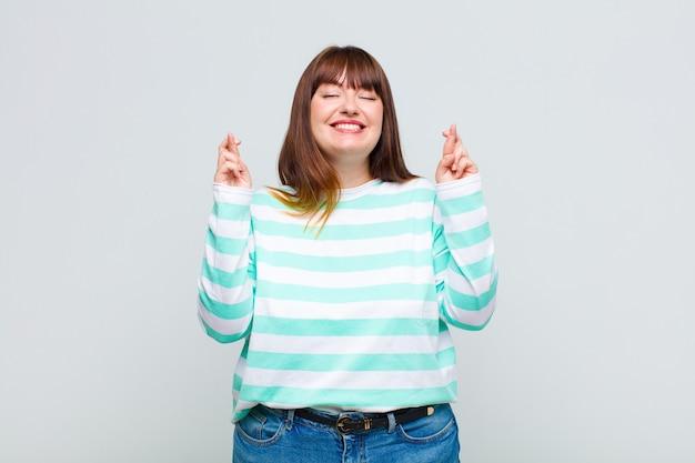 과체중 여성이 웃고 두 손가락을 애타게 꼬고 걱정하고 소원을 빌거나 행운을 바라고 있습니다.