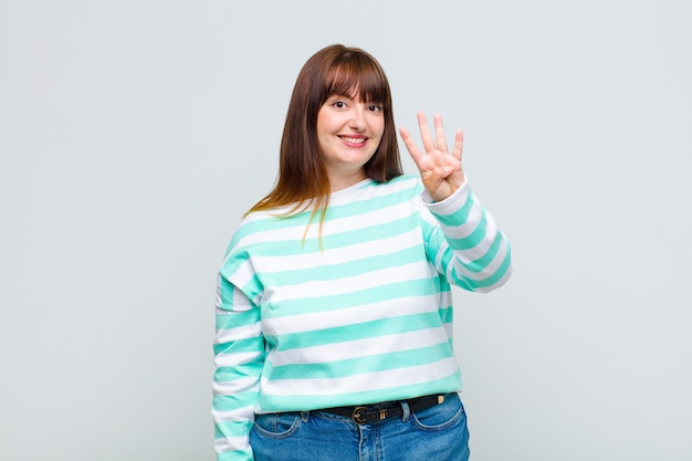 과체중 여성 미소하고 친절하게보고, 앞으로 손으로 4 번 또는 4 번을 보여주는, 카운트 다운