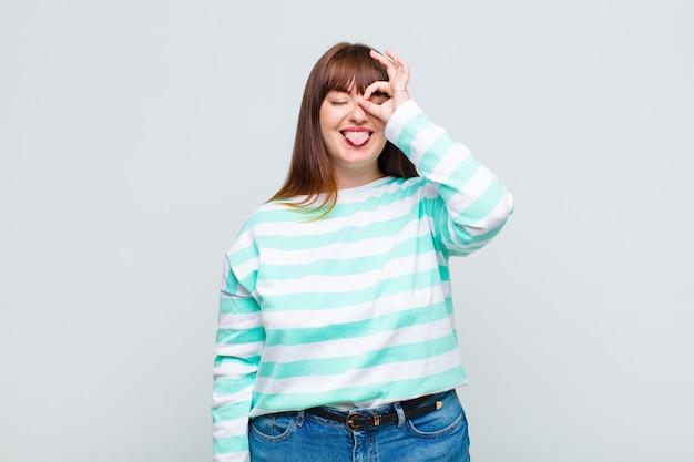 과체중 여성이 웃기는 얼굴로 행복하게 웃고, 농담하고 구멍을 통해보고, 비밀을 감시합니다.