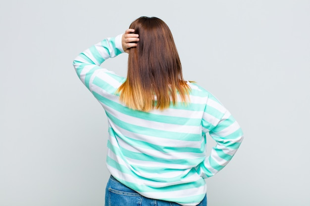 Женщина с избыточным весом думает или сомневается, почесывает голову, чувствует недоумение и замешательство, вид сзади или сзади