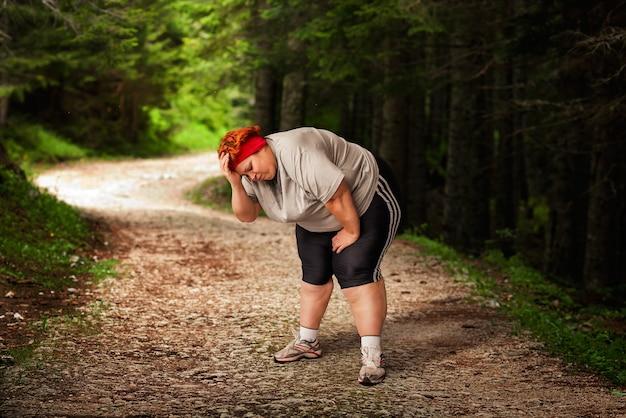 Женщина с избыточным весом устала после пробежки в лесу.