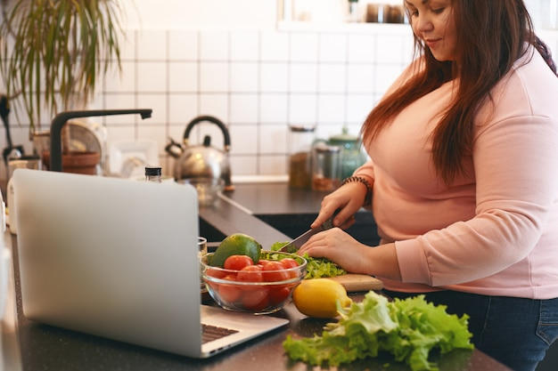 Overweight woman using laptop to watch video recipe while making vegan vitamin avocado salad, slicing leaf lettuce on wooden cutting board. healthy food, weight loss, dieting and nutrition concept