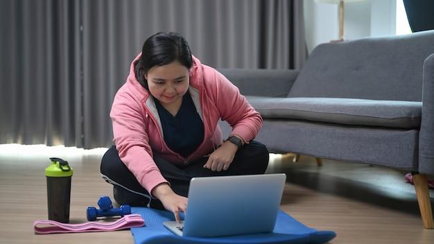 집에서 노트북에 온라인 운동을보고 중량이 초과 된 여자.
