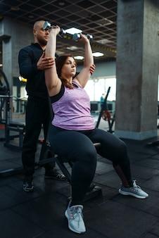 スポーツクラブでダンベルを使った運動、インストラクターとのフィットネストレーニングを行うトレーナーと太りすぎの女性。太りすぎ、肥満に対する有酸素運動、ジムに悩む女性