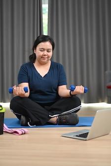 ダンベルで運動をし、ラップトップでフィットネストレーニングビデオを見ている太りすぎの女性。
