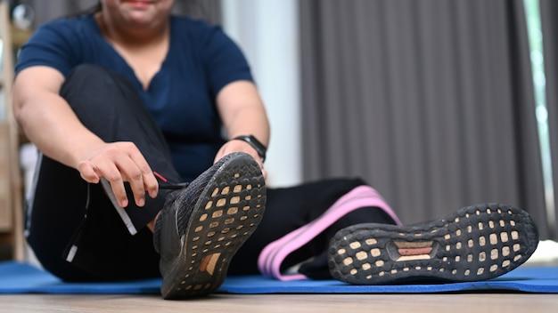 運動の準備をしている靴紐を結ぶ太りすぎの女性。