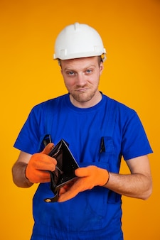 보호 헬멧에 중량이 초과 된 작업자는 빈 지갑을 보여줍니다. 경제의 불황. 돈이없는 죄수 복을 입은 남자. 경기 침체와 경제 위기, 실업
