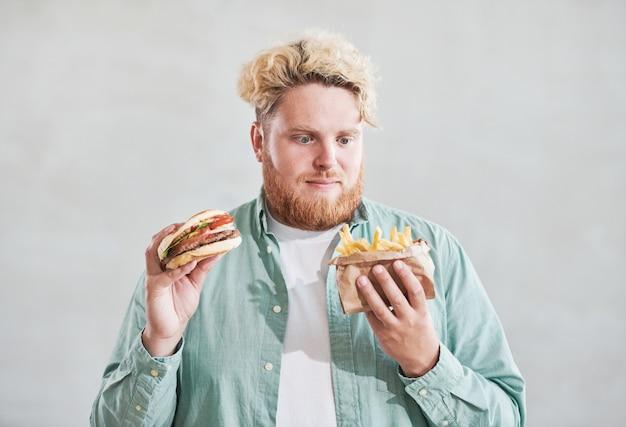 흰색 배경에 격리된 한 손에는 감자튀김을, 다른 손에는 햄버거를 들고 있는 과체중 청년
