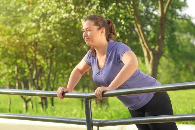 공원에서 운동하는 중량이 초과 된 젊은 여자. 체중 감량 개념