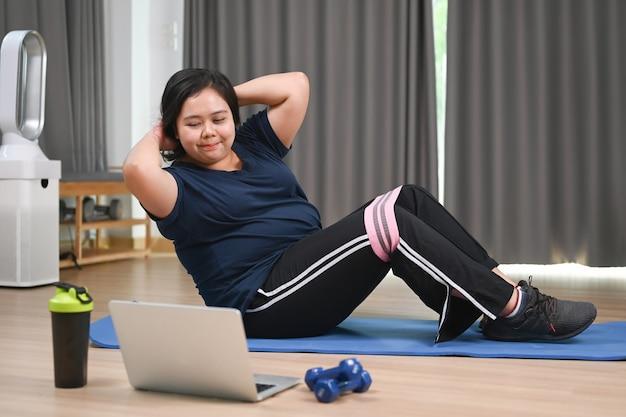 Полная молодая женщина смотрит видео тренировки фитнеса на компьтер-книжке и делает приседания на циновке дома.