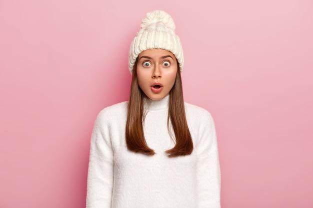 압도적 인 놀란 여자는 두려움에서 입을 벌리고, 깜짝 놀라며, 카메라를 응시하고, 분홍색 배경 위에 절연 된 퐁퐁과 스웨터가 달린 흰색 모자를 쓰고 있습니다.
