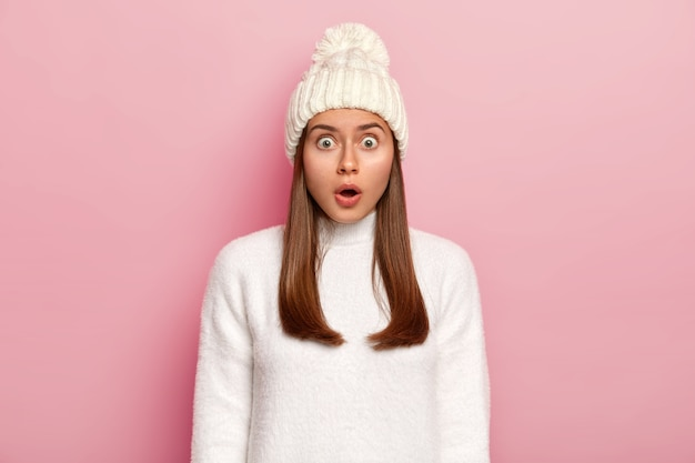 Overwhelmed astonished woman keeps mouth opened from fear, gasps amazed, stares at camera, wears white hat with pompon and sweater, isolated over pink background