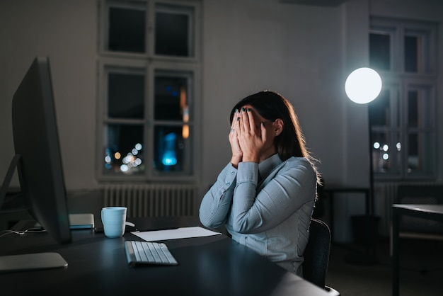 Overwhelmed businesswoman holding head in hands while working overtime at office desk.