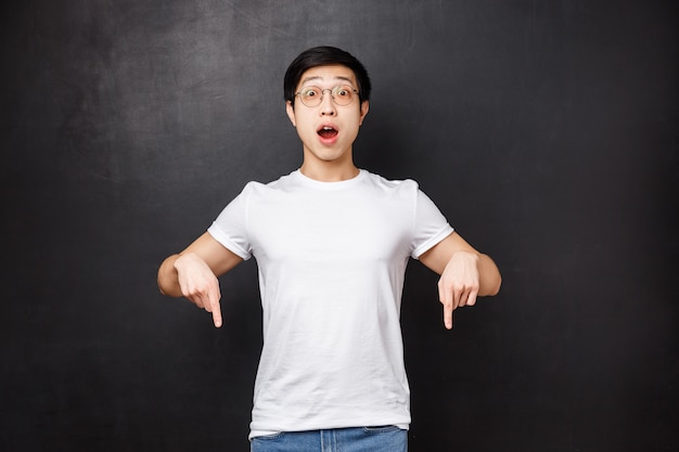Overwhelmed and excited asian guy in glasses losing his mind over thrilling cool new game, pointing fingers down showing friends what he got with special discount,