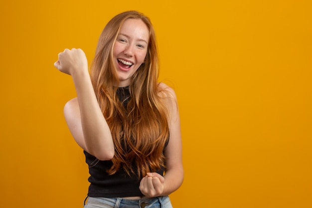 Overwhelmed excited smiling, happy redhead girl celebrating amazing news, achieve victory, winning competition, triumphing as become champion, gain goal or unexpected lucky event happened. on yellow.
