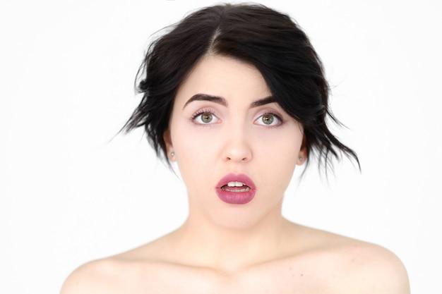 Потрясенная, озадаченная, потрясенная, удивленная, изумленная женщина на белой стене.